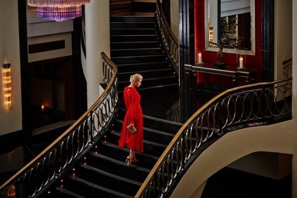 Frau auf der Lobbytreppe des Corinthia Hotels