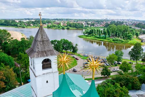 Kirchturm vor Fluss und Stadtpanorama